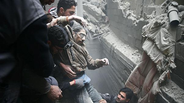 Civil defence help a man from a shelter in the besieged town of Douma