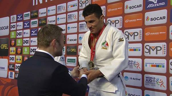 Saeid Mollaei of Iran receives gold from 2008 Olympic champion Ole Bischof