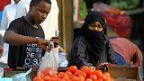 مرأة تشتري بندورة (طماطم) في سوق بجدة