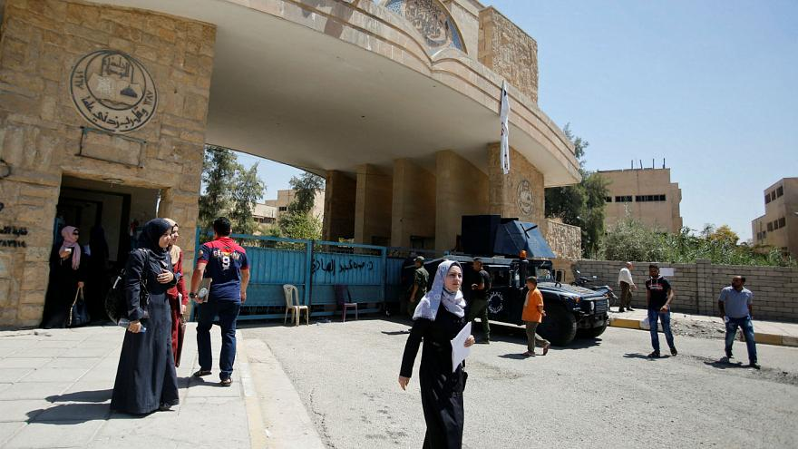University of Mosul students walk outside the campus in Mosul