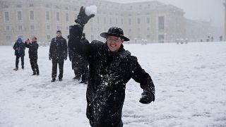 كاهن شاب يرمي كرة الثلج أمام ساحة القديس بطرس