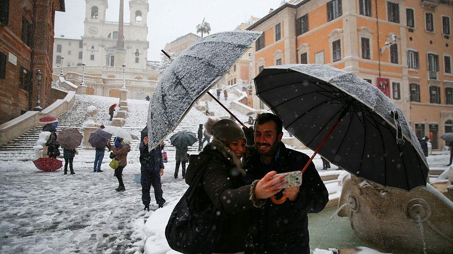 مواطنان يلتقطان صورة شخصية بجهاز محمول مع الثلج في روما