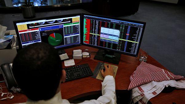 سعودي يعمل أمام شاشة حاسوب