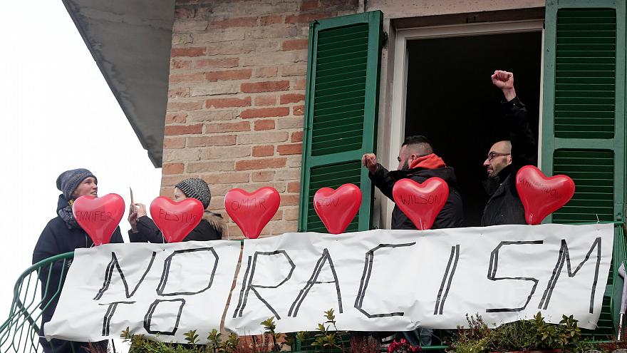 Demonstrators stand on a balcony during an anti-racism rally in Macerata.