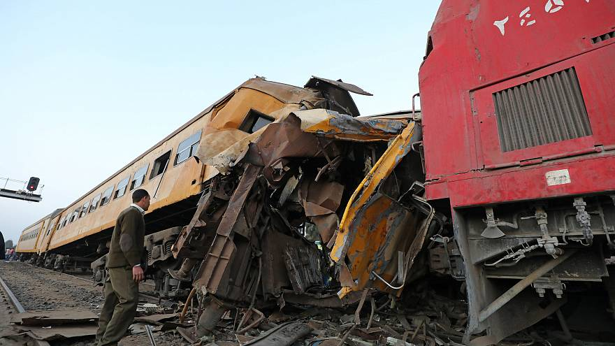 A policeman looks at the wreckage after a train crash in Kom Hamada