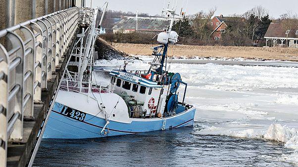 A híd alá szorított egy halászhajót a jeges víz Dániában