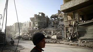 a boy walks near damaged buildings in the besieged town of Douma