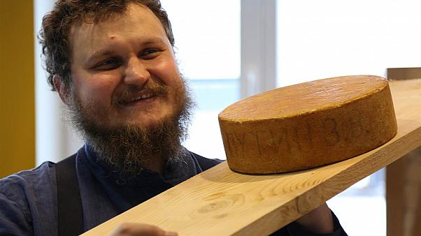 Oleg Sirota shows off a wheel of Russian-made mountain cheese