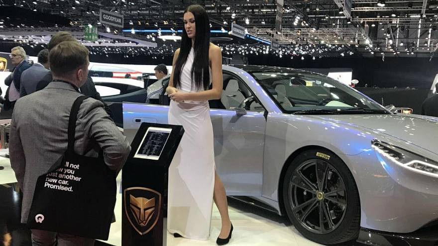 Un mannequin pose devant une voiture au salon de l'automobile à Genève