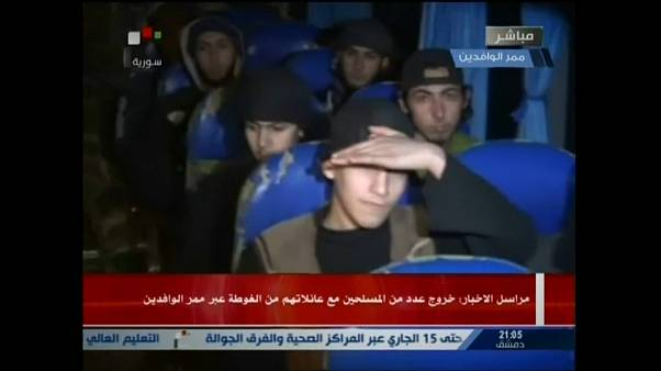 Report on Syrian TV shows small group boarding bus to leave