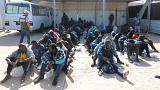 Migrants are seen at a naval base after being rescued by the Libyan coast