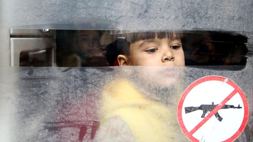 A boy looks through a bus window during evacuation from Douma, Syria