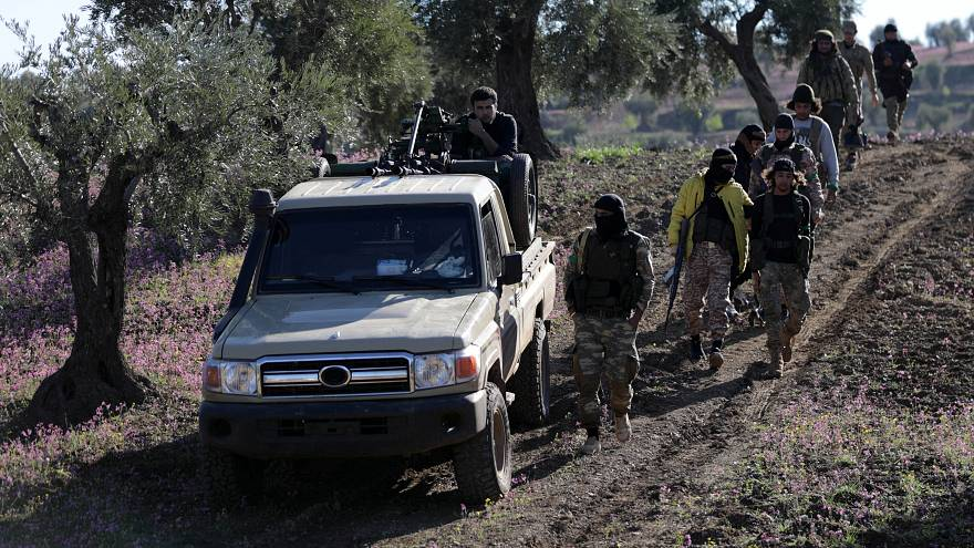 Turkish-backed Free Syrian Army fighters walk together after advancing