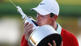 Rory Mcllroy holds the Arnold Palmer trophy