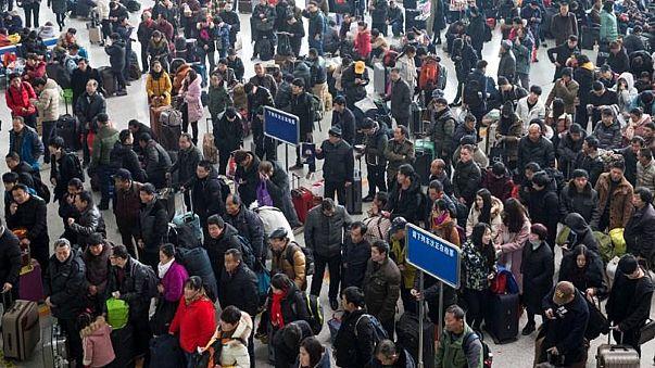 مسافرون ينتظرون في محطة قطارات في الصين