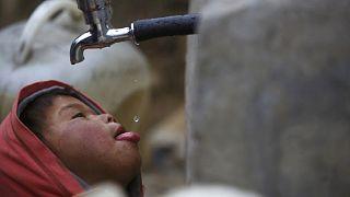 طفل يشرب قطرات من ماء ينساب من صنبور في نيبال