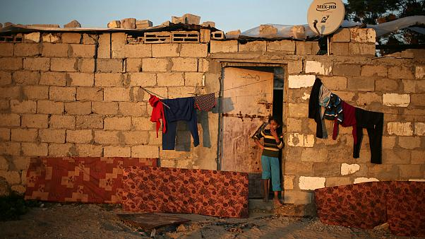 A Palestinian girl stands outside her family house in Gaza