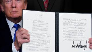 President Trump holds a signed memo on tariffs on hi-tech goods from China