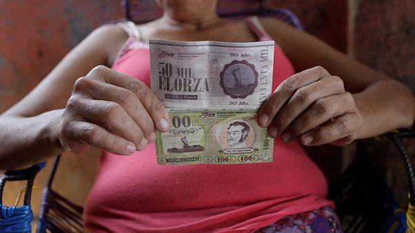 Una mujer muestra billetes de Elorza en su casa, Venezuela, el 19 de marzo
