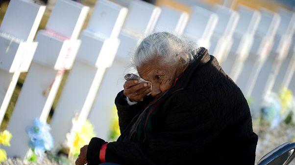 Una anciana llora junto a una de las tumbas