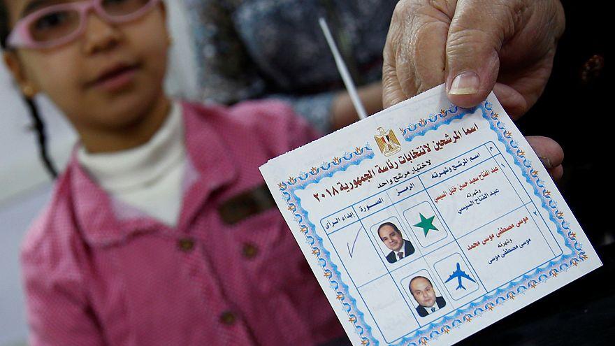 Una donna, in compagnia della figlia, mostra la tessere elettorale egiziana