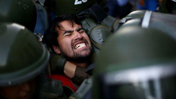 Un manifestant est retenu par la police lors d'une manifestation à Santigo
