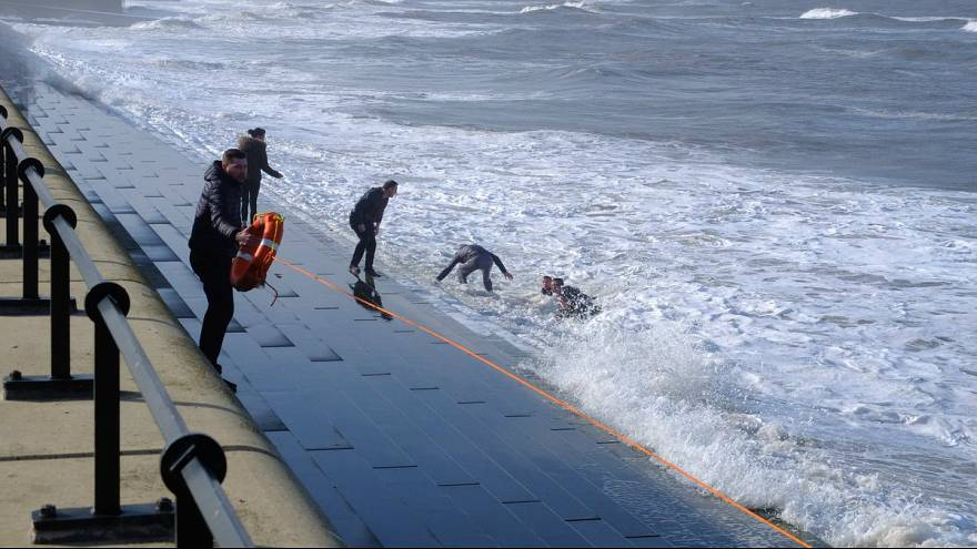 Human chain rescues four from rough seas at seaside resort