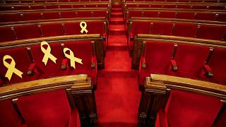 Ribbons on seats of imprisoned deputies at Catalonia's parliament, March 24