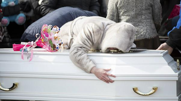 A woman reacts during a funeral of a victim from the shopping mall fire.