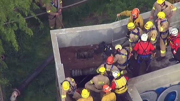 عمال إنقاذ يساعدون صبيا على الخروج من حفرة علق فيها في لوس أنجليس