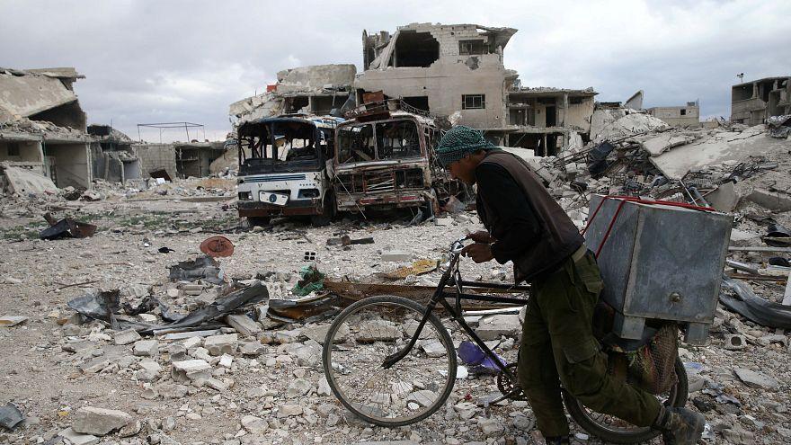 رجل يسير وبجواره دراجته الهوائية في موقع مدمر في دوما بغوطة دمشق