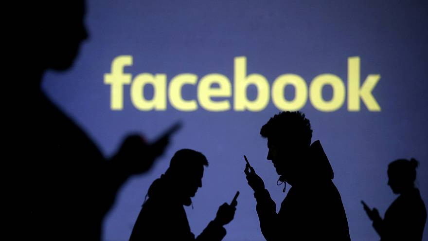 Mobile users are seen next to a screen projection of the Facebook logo.