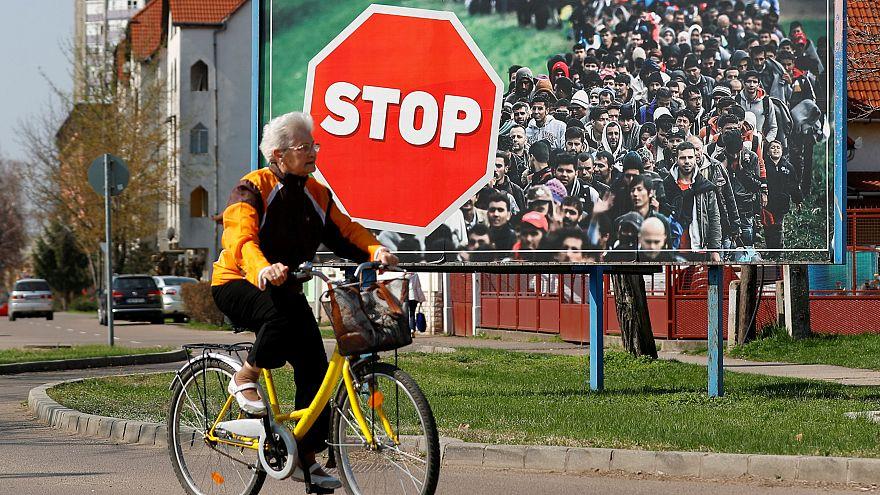 Eleitora passa diante de um cartaz do Fidesz contra a entrada de refugiados