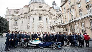 Pope Francis poses next a Formula-E electric racing car