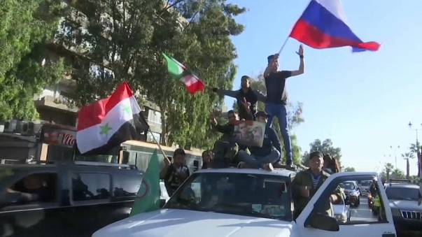 Syrians gather along the streets of Damascus to condemn the air strikes
