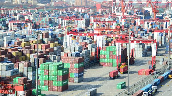Shipping containers are seen piled up at a port in Qingdao