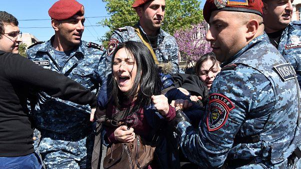 Eine junge Demonstrantin wird am Montag bei Protesten aufgehalten.