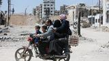 A Syrian family rides along a damaged street in Douma, Damascus.