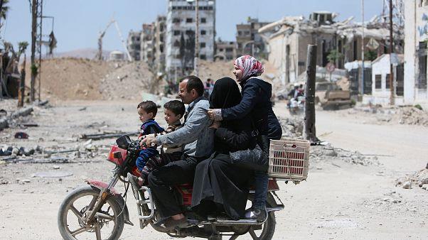 A Syrian family rides along a damaged street in Douma, Damascus.