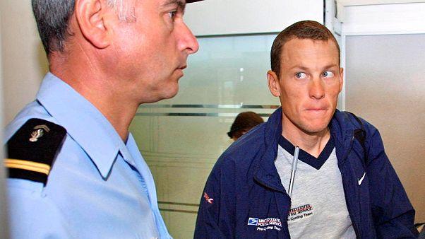 Lance Armstrong 2001-ben egy csendőr mellett a grenoble-i repülőtéren