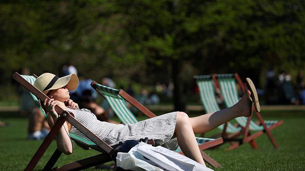 Londra'da St James Parkı'nda şezlonglarda güneşlenen bir kadın