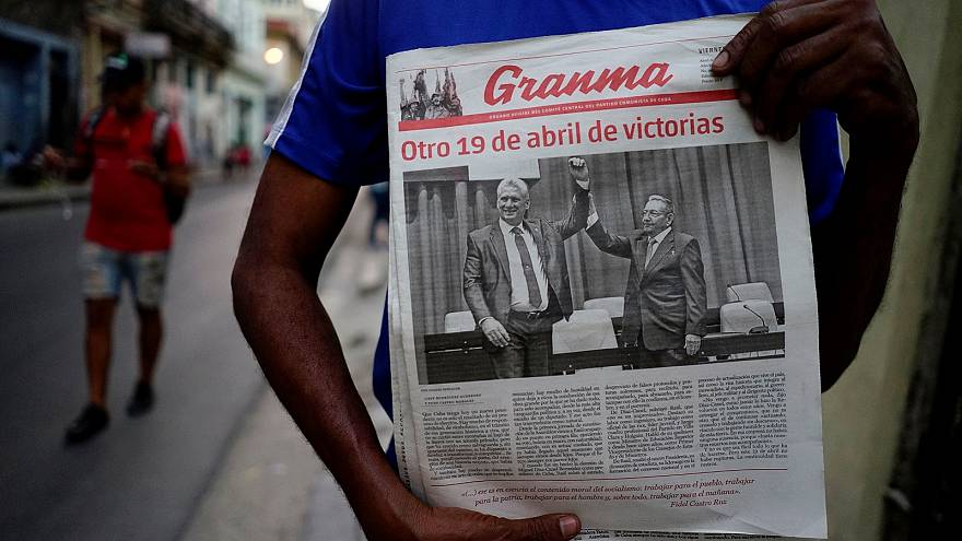 A man holding a newspaper marking the transition of power