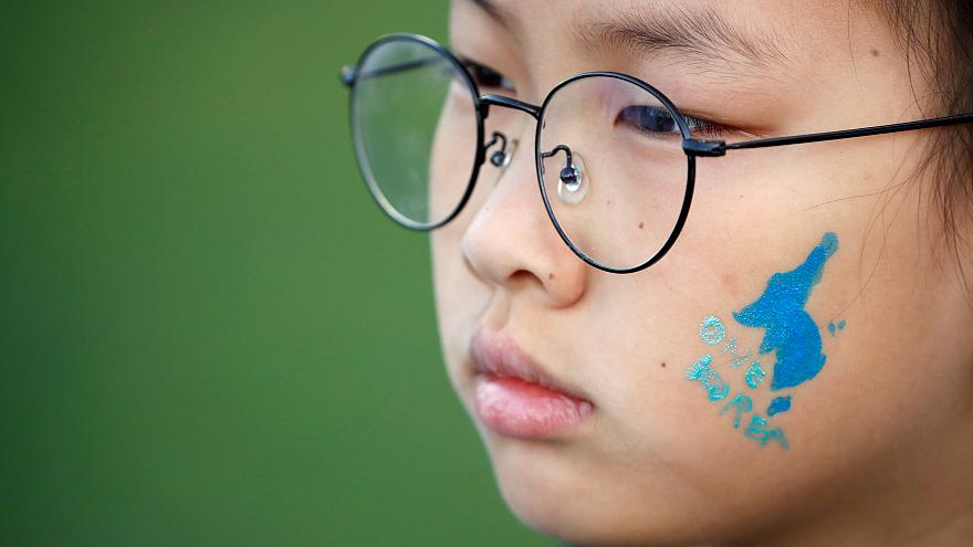 A blue silhouette of the Korean peninsula on childs face