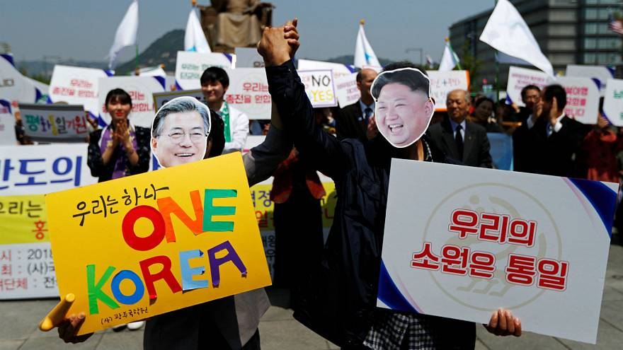 People hold hands as they wear masks of South Korea's President Moon Jae-in