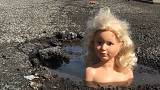 Dolls' heads pop up in UK potholes in repair plea