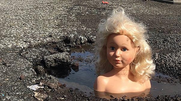 Dolls' heads pop up in UK potholes in repair plea