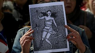 A woman holds up a picture as other shout slogans during a protest