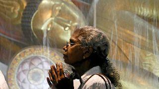 Mulher reza num templo budista do Sri Lanka