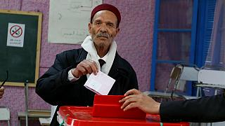 Um tunisino deposita o voto numa urna de Tunis