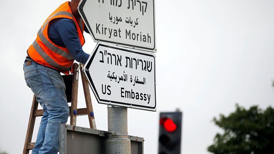 Ein Arbeiter bringt eines der Straßenschilder an